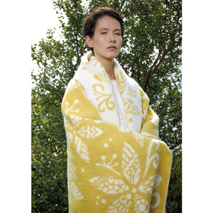 A woman wearing a floral printed yellow and white Lopi Wool Blanket.