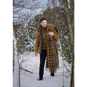 A man in the snow in Iceland wearing a brown plaid Lopi Wool Blanket.