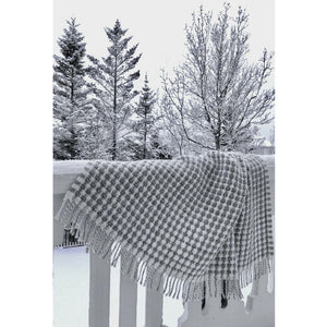 A winter christmas scene in Iceland with a white and grey Lopi wool blanket hanging on the railing.