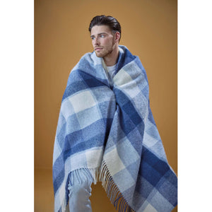A man wearing a blue plaid Lopi Wool Blanket.
