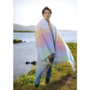 A woman in Iceland with a pastel Lopi blanket draped on her shoulders.