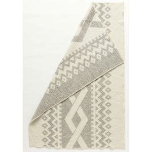 Flétta, a reversible Lopi Icelandic wool blanket with light grey and white geometric shapes.