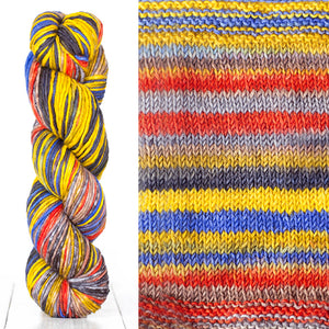 Color 4015: a hand-dyed skein of self striping wool yarn with yellow, red, blue, and grey shades
