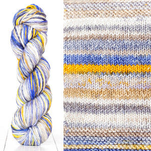 Color 4016: a hand-dyed skein of self striping wool yarn with white, grey, yellow, and blue shades