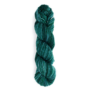 A twisted hank of Monokrom Worsted in color 4065, a deep, tonal, blue green.