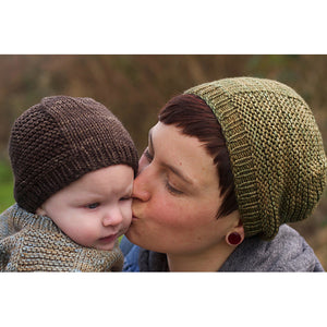 A young woman holding a baby, both wearing Barley Hats.