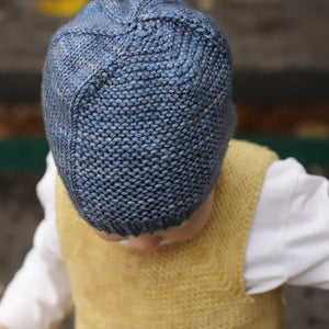 The top and front of the Barley Hat on a young child looking down.