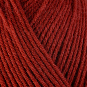 Kabocha 3327, a red-orange skein of washable worsted weight Ultra Wool yarn.