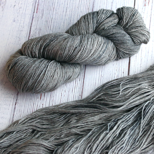 A twisted hank of Plymouth Yakima Yarn in Pewter grey