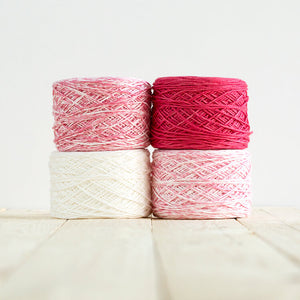 Gradient #500, 4 cakes of yarn fading from a bright reddish pink to white.