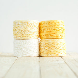 Gradient #502, 4 cakes of yarn fading from a cheery warm yellow to white.