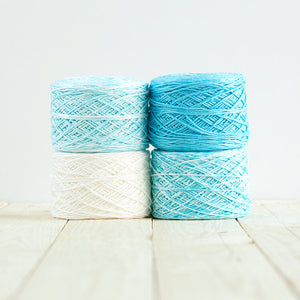 Gradient #505, 4 cakes of yarn fading from a bright cyan blue to white.