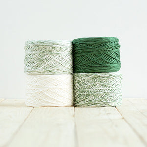 Gradient #509, 4 cakes of yarn fading from a forest green to white.