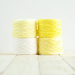 Gradient #516, 4 cakes of yarn fading from a lemon yellow to white.