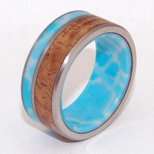 Liina Terra. This beautifully crafted, titanium wedding ring has a double offset inlay of Larimar Stone and Koa wood on the exterior. An interior overlay of Larimar stone. The Larimar stone is from the South West region of the Dominican Republic. We know you will love the delicate aqua-blue tones in this gorgeous Caribbean stone. Polished with a satin finish and complemented nicely with fully rounded edges.