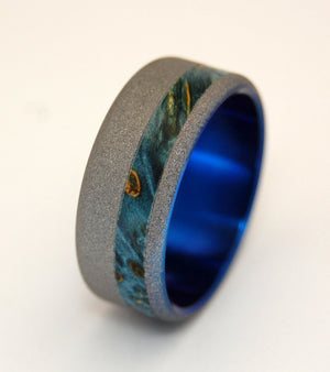 When the moon hits your eye... An offset Blue Box Elder inlay offers celestial energy, while a sandblast finish adds sparkling moon-rock luster. An anodized Sapphire Blue interior glows from within. Pictured at 7.9mm.