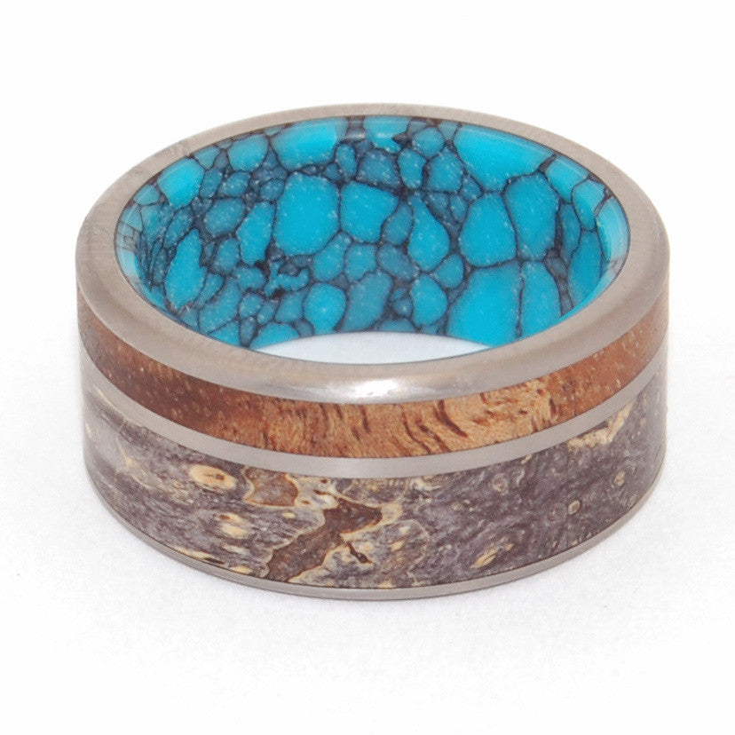 The Sea Beneath. This beautifully crafted, titanium wedding band has an offset double inlay of rich Koa wood and Black Box Elder wood, with an interior overlay of webbed turquoise. Brushed satin finish and fully rounded edges.  Weaving together these unique inlays, the heat of Hawaiian tropics gives life to the rich Koa wood; and the cool burst of webbed turquoise blue reminiscent of Siberian Lake Baikal. Here is an ode to love in all its form.