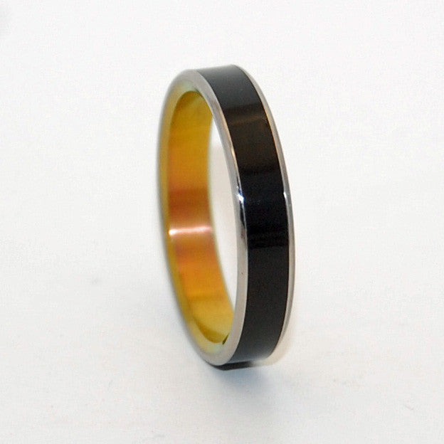 Black Onyx stone is center inlayed in this minimalist wedding ring. Interior is anodized with a bright sunset hue. Nicely polished with a mirror finish. Flat edges.