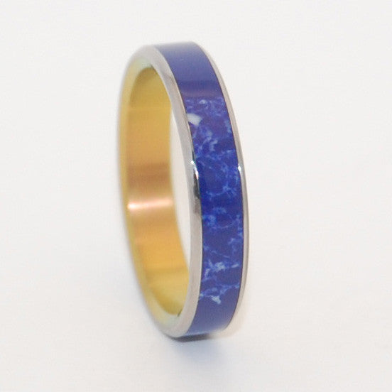 Sodalite stone is center inlayed in this modern wedding ring. Hints of white streaks makes this stone stand out. Interior is anodized with a bright sunset hue. Nicely polished with a mirror finish. Flat edges. Pictured at 4mm.