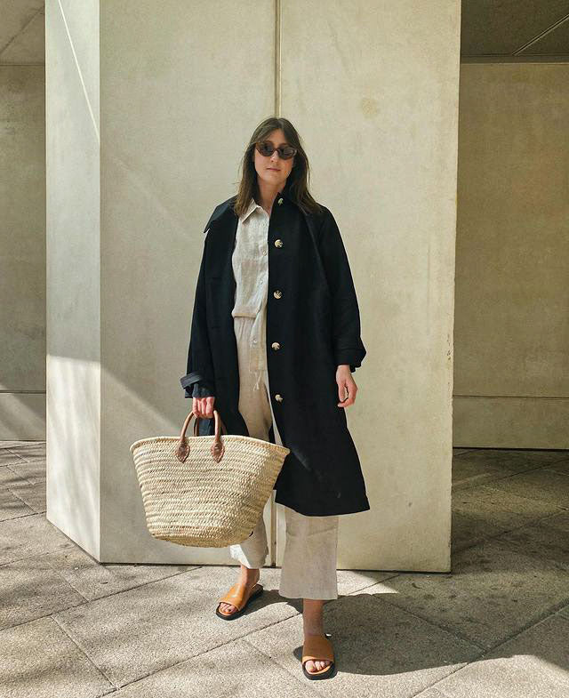 Woman in a navy trench coat and sunglasses holding a Bohemia Design basket