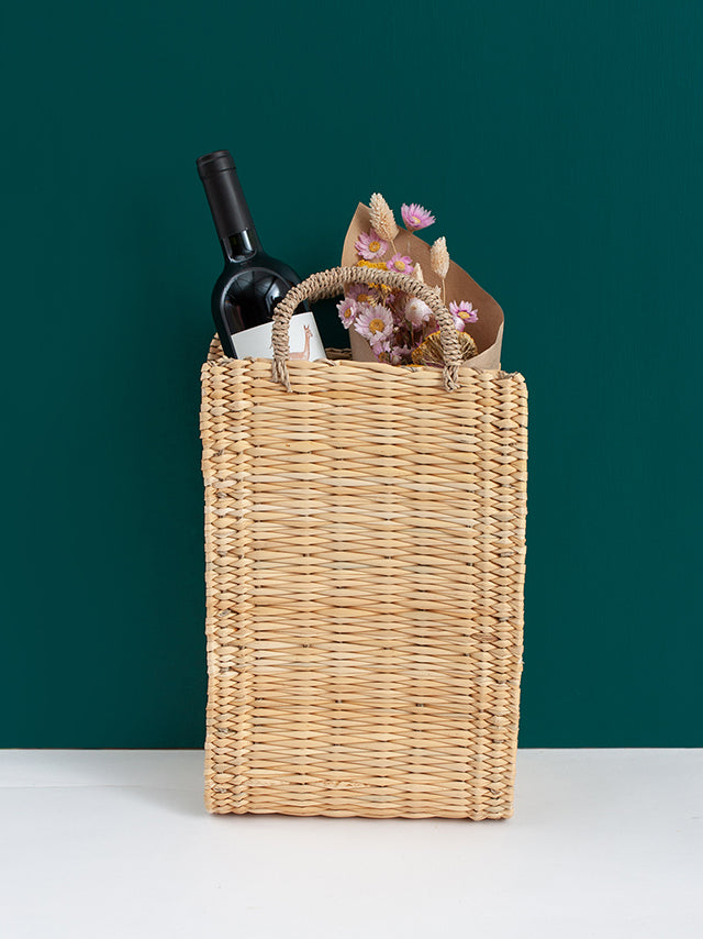 Tall reed basket with dried flowers and a bottle of wine against a green background