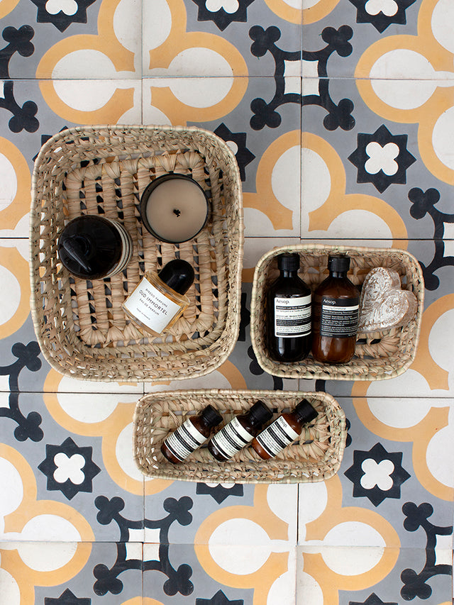 Set of 3 woven storage trays filled with toiletries against Moroccan tiles