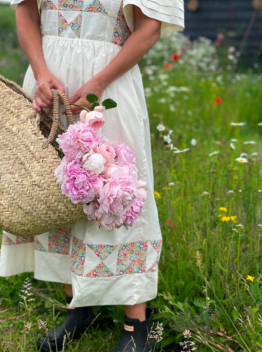 Woman in a white dress holding a Bohemia Design basket filled with pink flowers