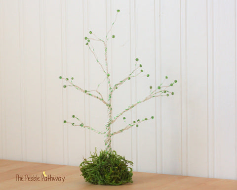 Green and white wire tree with emeraled colored beads and preserved moss base