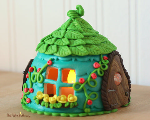 teal blue fairy house with green leaf roof tea light yellow and pink flowers vines fairy door with window 0244