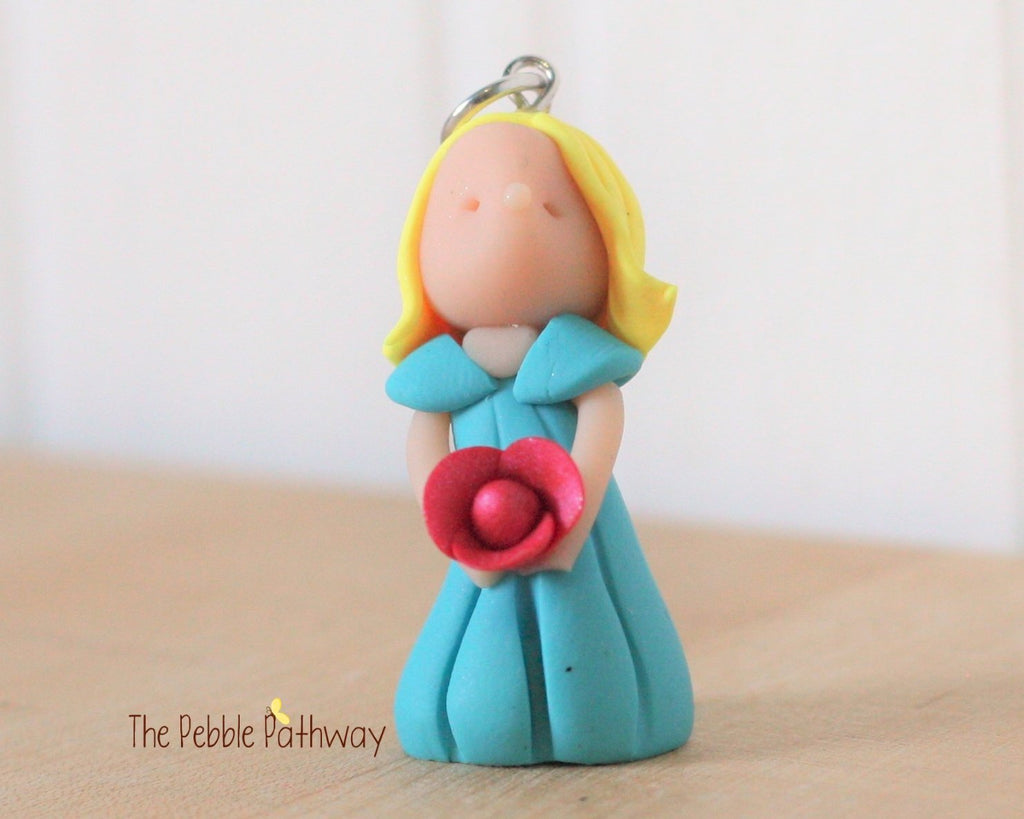 fairy ornament with short blonde hair blue dress and pink flower 0288