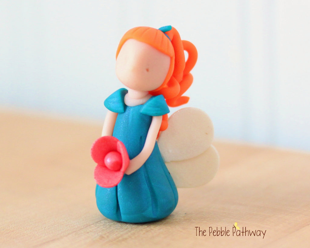 Armelle the Miniature Ginger Winged Fairy with long red hair and blue dress holding pink flower - ThePebblePathway