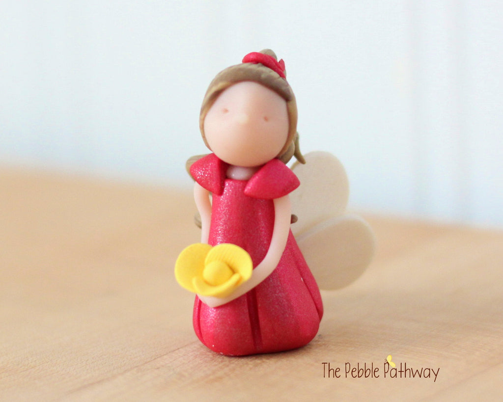 Grecia the Miniature Winged Fairy with long light brown hair and pink dress holding yellow flower - ThePebblePathway
