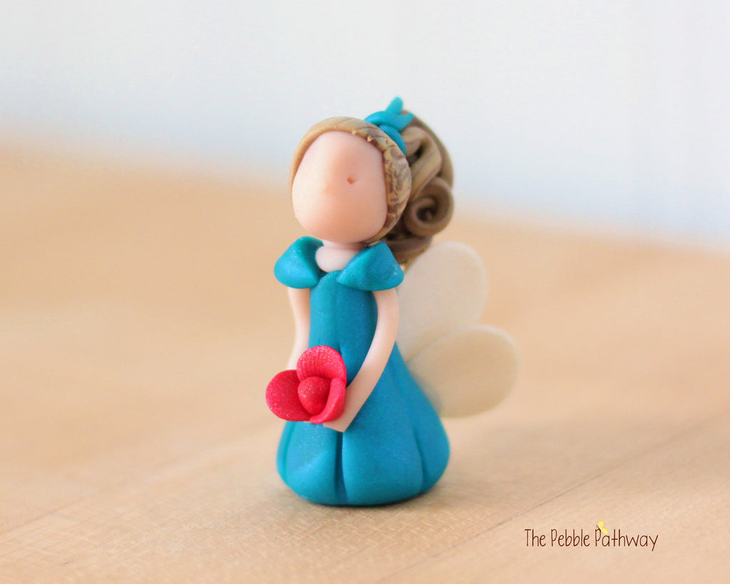 Braelynn the Miniature Winged Fairy with long light brown hair and blue dress holding pink flower - ThePebblePathway