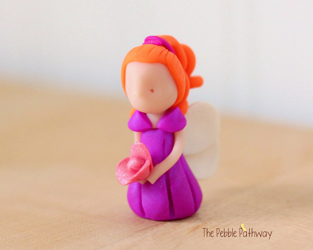 Delaney the Miniature Ginger Winged Fairy with long red hair and purple dress holding pink flower - ThePebblePathway