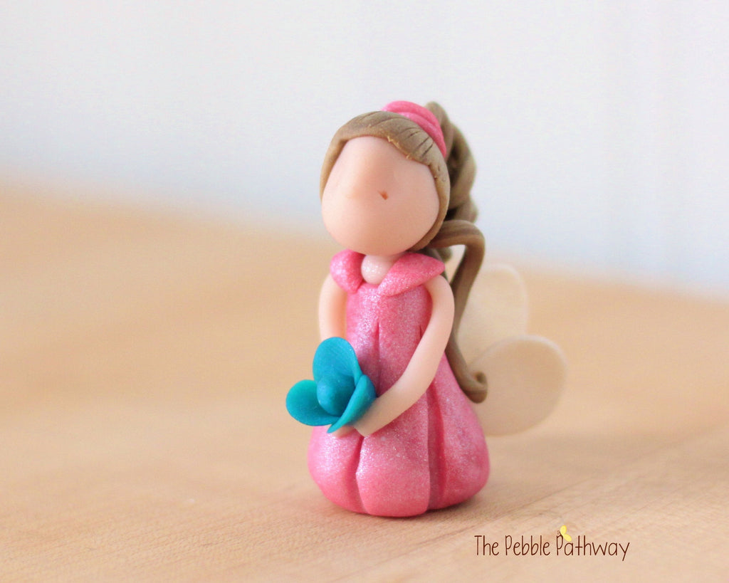Darby the Miniature Winged Fairy with long light brown hair and pink dress holding blue flower - ThePebblePathway