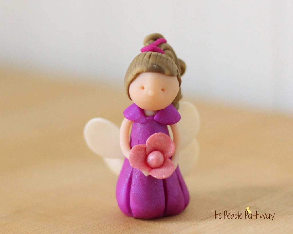 Gracen the Miniature Winged Fairy with long light brown hair and purple dress holding pink flower - ThePebblePathway
