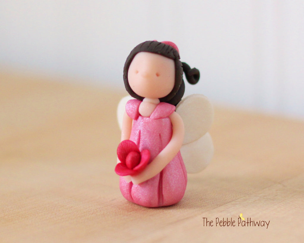 Gianna the Winged Fairy with long brown hair and pink dress holding pink flower - ThePebblePathway