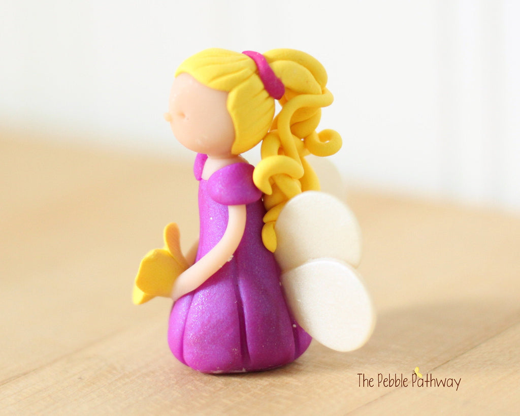 Miniature Winged Fairy with long blonde hair and purple dress holding yellow flower 0550 - ThePebblePathway
