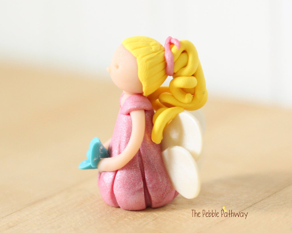 Miniature Winged Fairy with long blonde hair and pink dress holding blue flower 0551 - ThePebblePathway