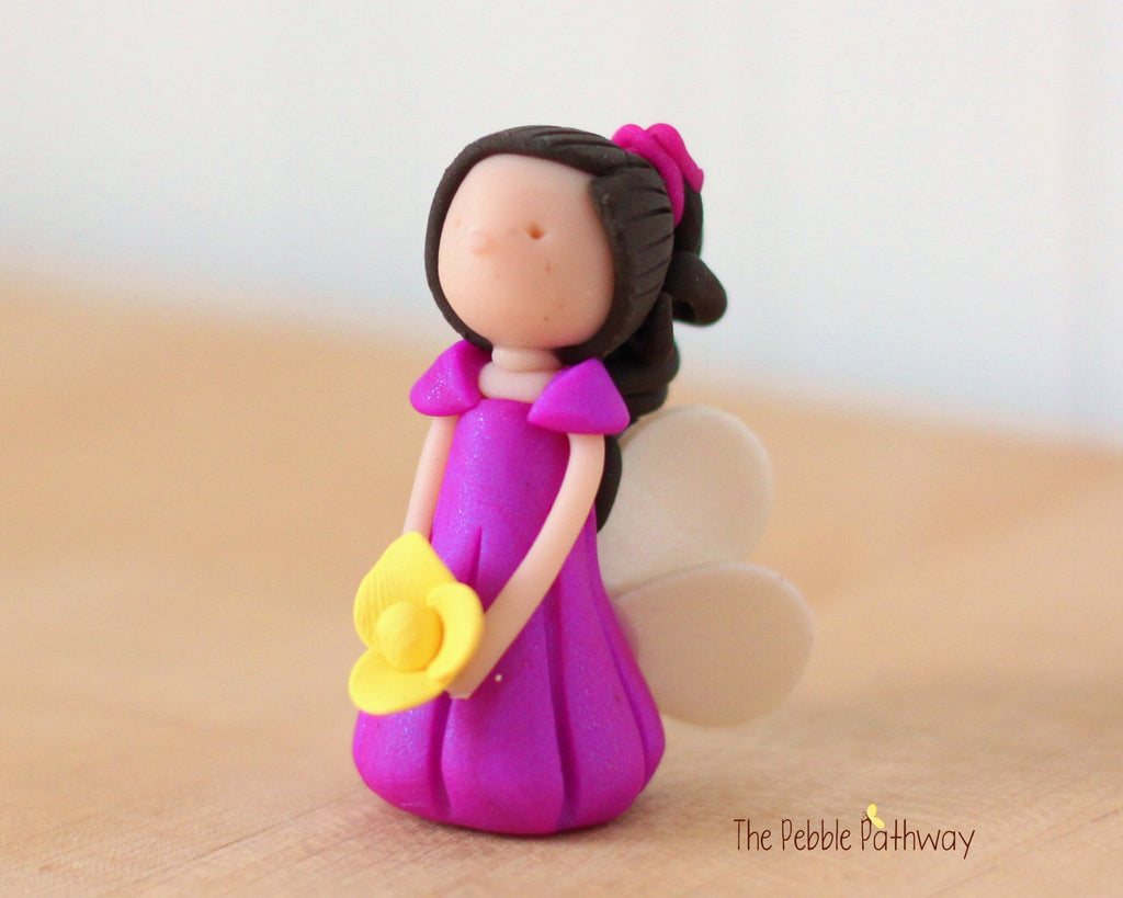 Adley the Miniature Winged Fairy with long brown hair and purple dress holding yellow flower - ThePebblePathway