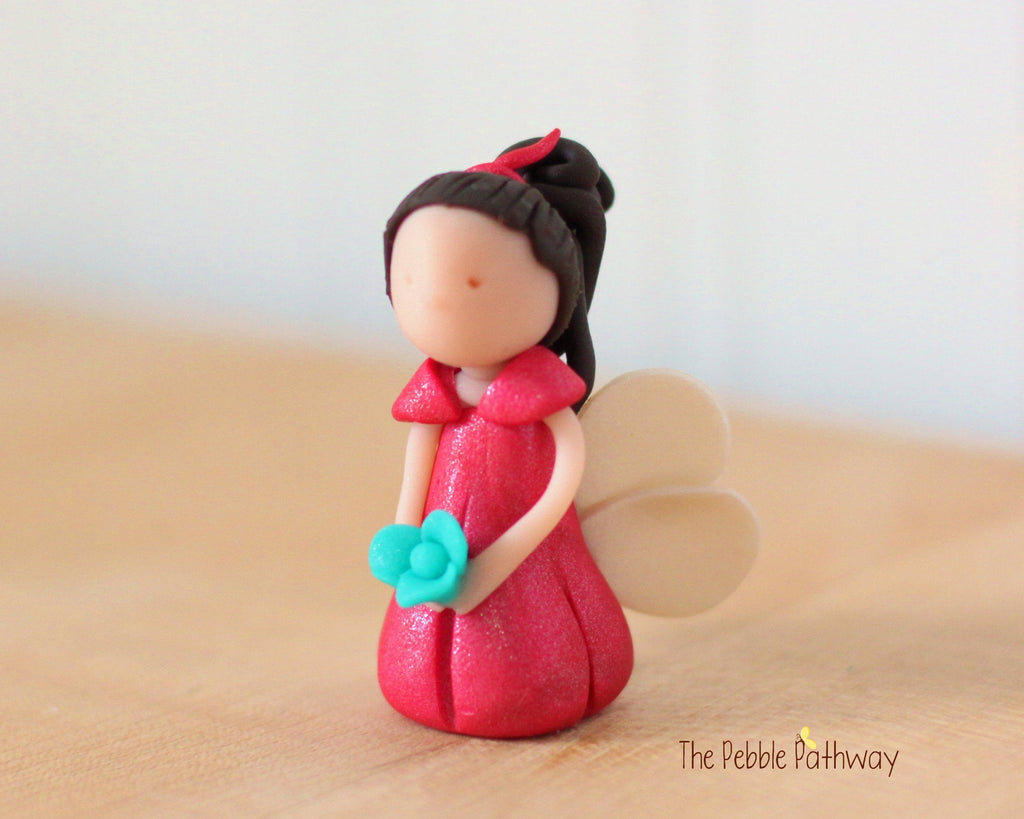 Royce the Miniature Winged Fairy with long brown hair and pink dress holding blue flower - ThePebblePathway