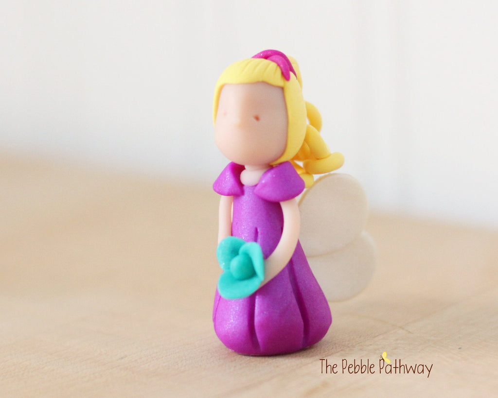 Waverly the Miniature Blonde Winged Fairy with long blonde hair and purple dress holding blue flower - ThePebblePathway