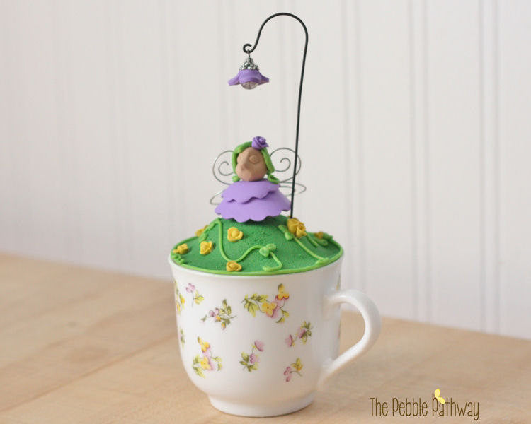 Tea Cup fairy garden - purple and yellow flowers and fairy - ThePebblePathway