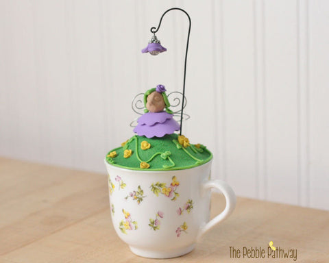 tea cup fairy garden purple and yellow flowers and fairy