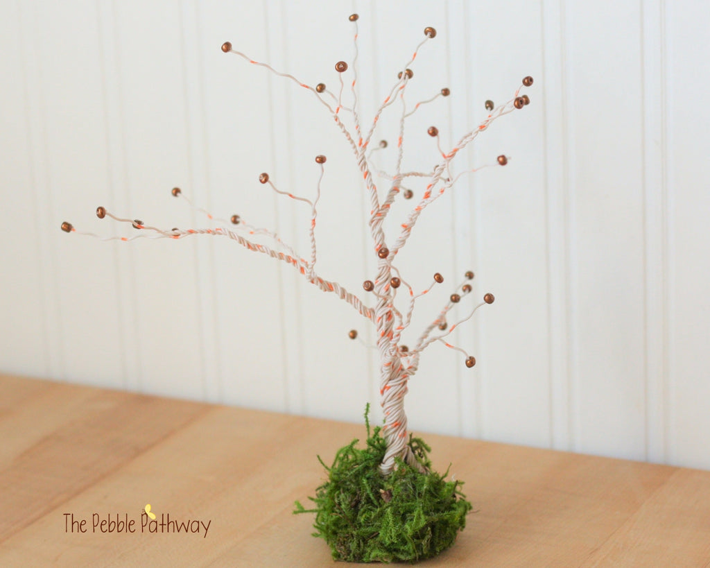 Orange and white wire tree with copper colored beads and preserved moss base