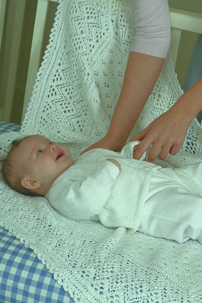 Baby on a knitted blanket wearing a white cardigan