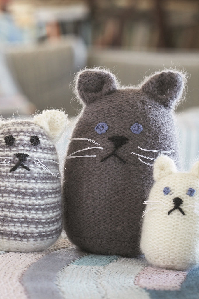 Three knitted cats of different sizes, two plain and one striped