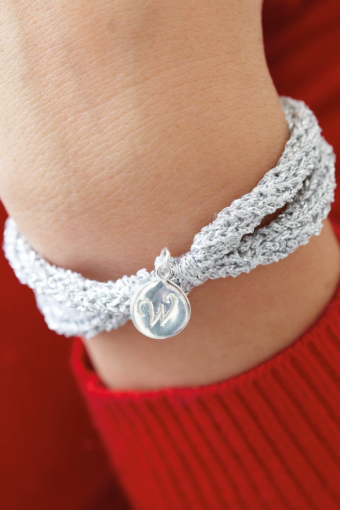 Silver knitted bracelet with charm attached