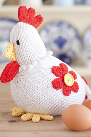 Knitted chicken with bright red comb on head and flower motif