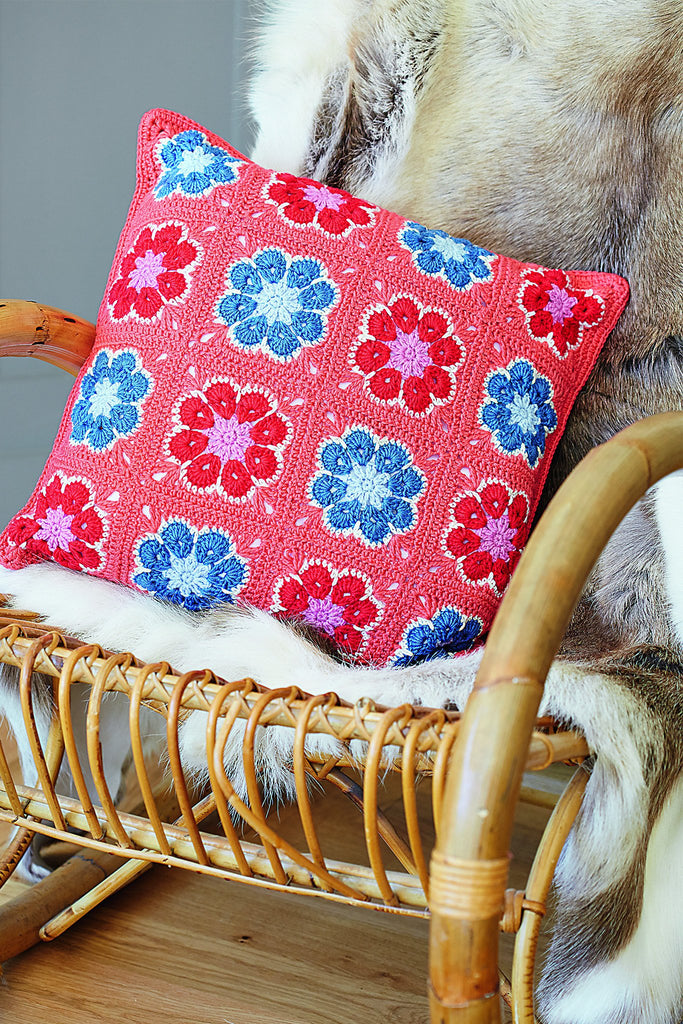 Crocheted coral cushion with pink and blue flowers